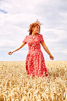 Beautiful red-haired woman in a wheat field - p1540m2200536 by Marie Tercafs