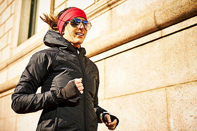 Woman jogging in city - p343m2046933 by Josh Campbell