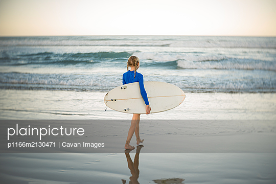 Young girl carrying surfboard at a beach in New Zealand - p1166m2130471 by Cavan Images