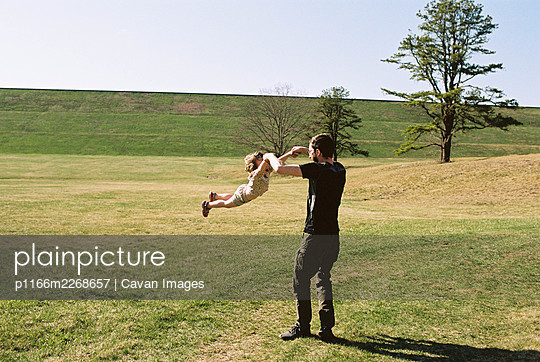 A little girl and her father playing in a grassy field by a dike - p1166m2268657 by Cavan Images