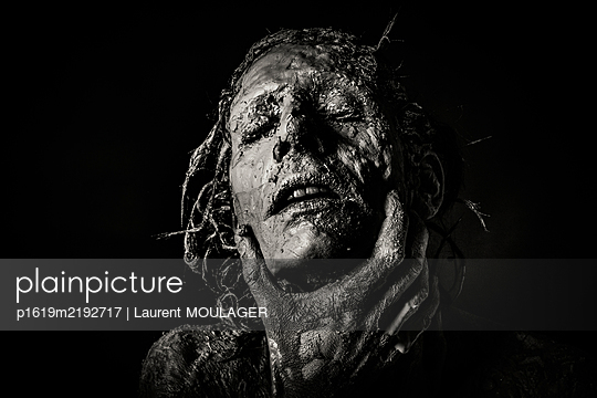 Woman face covered with clay with man's hand holding her jaw - p1619m2192717 by Laurent MOULAGER