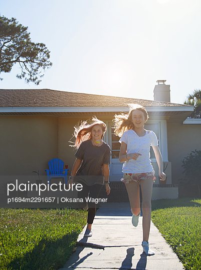 Two happy sisters having fun outside next to the house  - p1694m2291657 by Oksana Wagner
