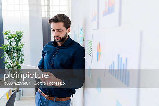 Young businessman using digital tablet while leaning on wall in office - p300m2251487 by Giorgio Fochesato