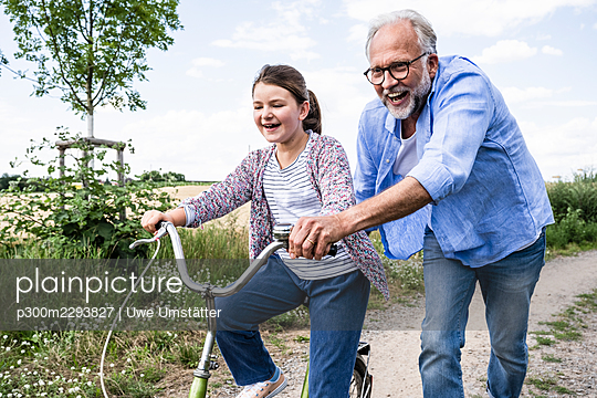 Cheerful grandfather playing with granddaughter cycling on dirt road - p300m2293827 by Uwe Umstätter