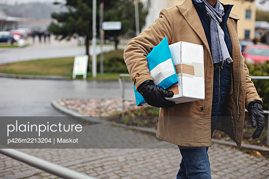 Midsection of senior man with package walking by sidewalk during winter - p426m2213204 by Maskot