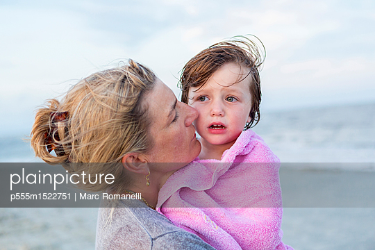 Caucasian mother holding son at beach - p555m1522751 by Marc Romanelli
