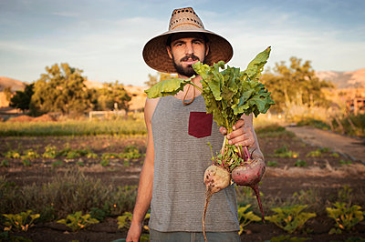 Portrait of confident male farmer holding freshly harvested beetroots on field - p1166m1052324f by Christian Ericksen