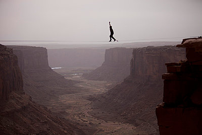 Andy Lewis working on a world record highline, three hundred and forty feet long, at the Fruit Bowl in Moab, Utah, USA - p3437222f by Jared Alden