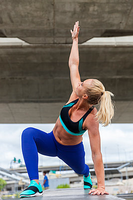 Woman in runners lunge. - p343m1443481 by Lucie Wicker