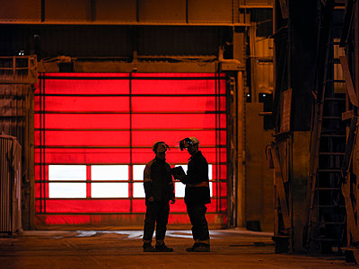 Steelworkers in discussion in steelworks - p429m1013709f by Monty Rakusen