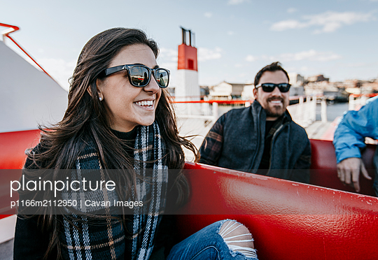 A young woman smiles while riding a ferry in the fall. - p1166m2112950 by Cavan Images