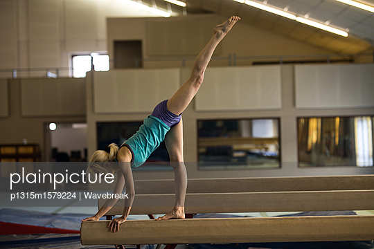 Female athletic balancing on wooden bar