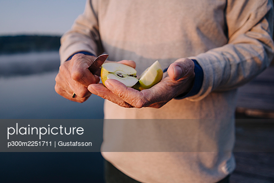 Man holding slice of apple while standing outdoors - p300m2251711 by Gustafsson