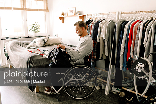 Side view of disabled mature man packing tennis racket in bag while sitting on wheelchair at home - p426m2101889 by Maskot