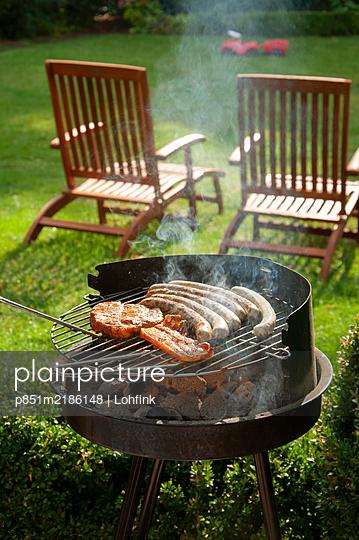 Fleisch grillen im Garten - p851m2186148 von Lohfink