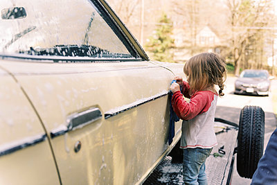 A father and his toddler daughter washing a classic car together. - p1166m2190671 by Cavan Images