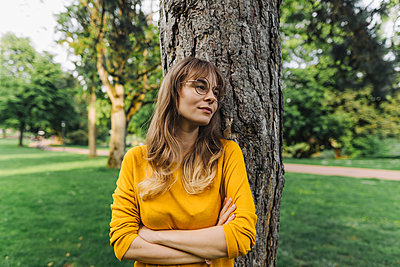 Young woman at a tree in park looking sideways - p300m2140450 by Kniel Synnatzschke