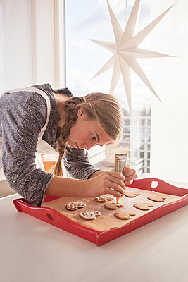 Girl decorating gingerbread cookies - p312m1472563 by Christina Strehlow