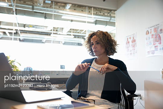 Portrait of mature female medical consultant in office with laptop - p1192m2123393 by Hero Images