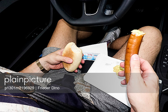 Man eating wiener in his car - p1301m2196929 by Delia Baum