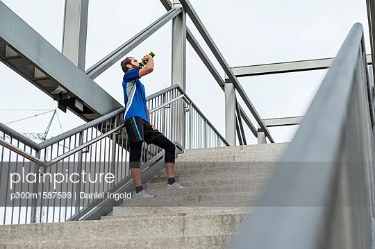 Man on stairs having a break from running - p300m1587599 von Daniel Ingold