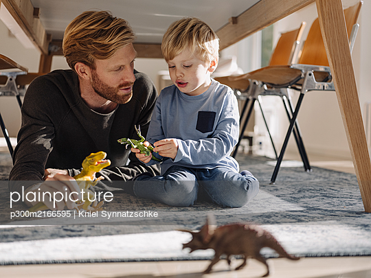 Father and son playing with dinosaur figures under the table at home - p300m2166595 by Kniel Synnatzschke