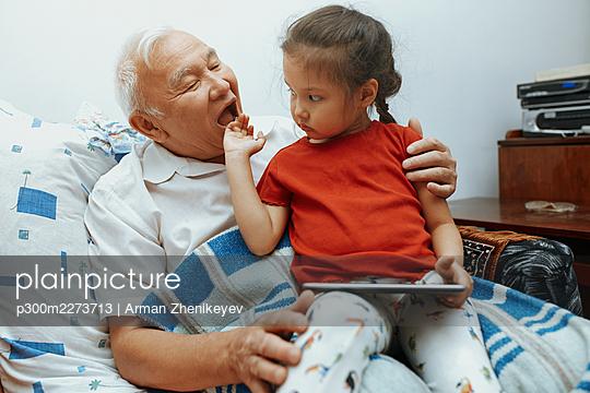 USA, Grandfather and granddaughter using tablet computer - p300m2273713 von Arman Zhenikeyev