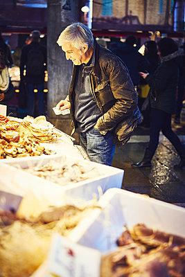 Mann mit Geldschein an einem Marktstand mit Muscheln - p1312m2082199 von Axel Killian