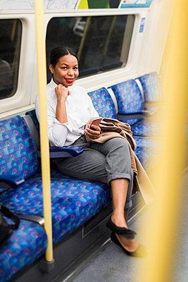 UK, London, portrait of smiling businesswoman with cell phone sitting in underground train - p300m1581061 von Mauro Grigollo