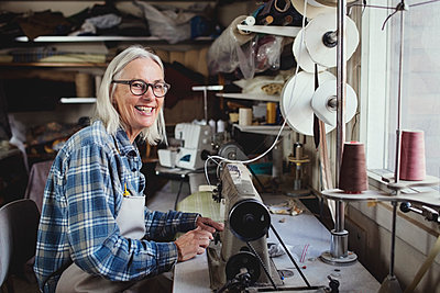 Portrait of smiling owner using sewing machine at workshop - p426m1543004 by Maskot