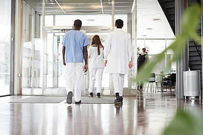 Full length rear view of healthcare workers walking in lobby at hospital - p426m2018982 by Maskot