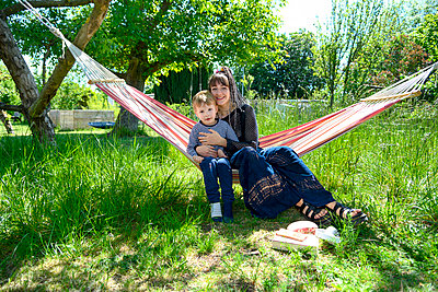 Young woman and toddler boy in a hammock - p427m2203612 by Ralf Mohr