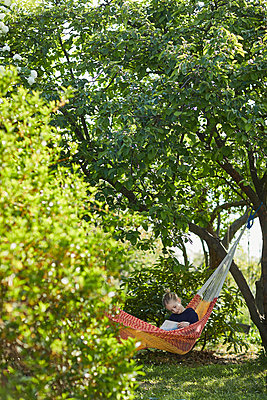 Girl in hammock reading a book - p300m2199264 by Maya Claussen