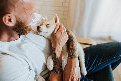 Mid adult man embracing dog while sitting on chair at home - p300m2243294 by Miguel Frias
