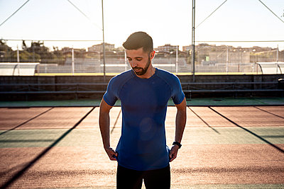 Male sportsperson standing on sports court during sunny day - p300m2250270 by Albert Martínez