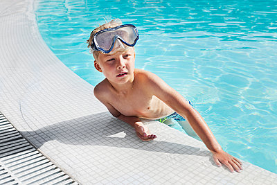 Boy wearing goggles in pool - p352m2121124 by Folio Images