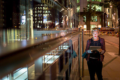 Mature woman using digital tablet on the move at night, London, UK - p429m999635 by dotdotred