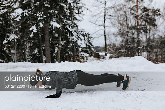 Woman doing push-ups at winter - p312m2299715 by Plattform