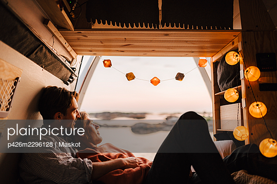 Gay couple looking away in motor home during camping - p426m2296128 by Maskot