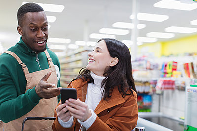 Grocer helping customer with smart phone in supermarket - p1023m2187663 by Sam Edwards