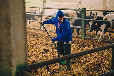 Young farmer wearing hood spreading straws in farm - p300m2242181 by Aitor Carrera Porté