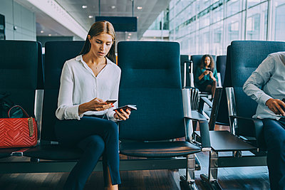 Young businesswoman text messaging through smart phone while sitting with passport in waiting room at airport - p426m2074775 by Maskot