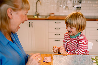 Happy grandson playing board game with grandmother at home - p426m2195048 by Maskot