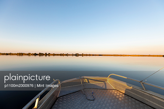 A boat on the waters of Okavango Delta at sunset, flat calm water - p1100m2300976 by Mint Images