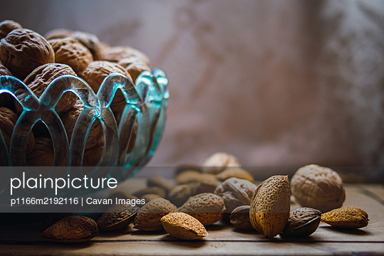 walnuts and almonds in a blue glass bowl on a rustic wooden table - p1166m2192116 by Cavan Images
