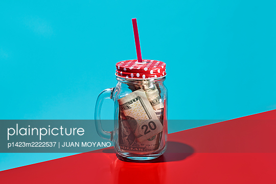 US dollar notes in a glass mug, on a red and blue background - p1423m2222537 by JUAN MOYANO