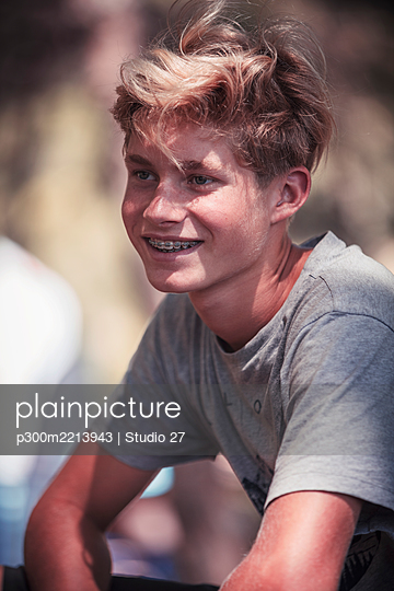 Teenage boy smiling while standing at beach - p300m2213943 by Studio 27