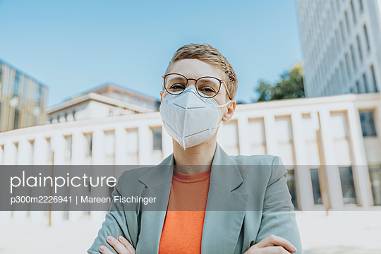 Mid adult woman wearing protective face mask standing on street during sunny day - p300m2226941 by Mareen Fischinger