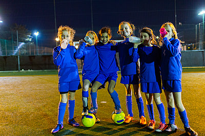 Portrait confident girls soccer team drinking water on field at night - p1023m2035233 by Paul Bradbury