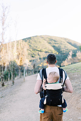 A young father hiking while carrying his son on his back. - p1166m2162789 by Cavan Images